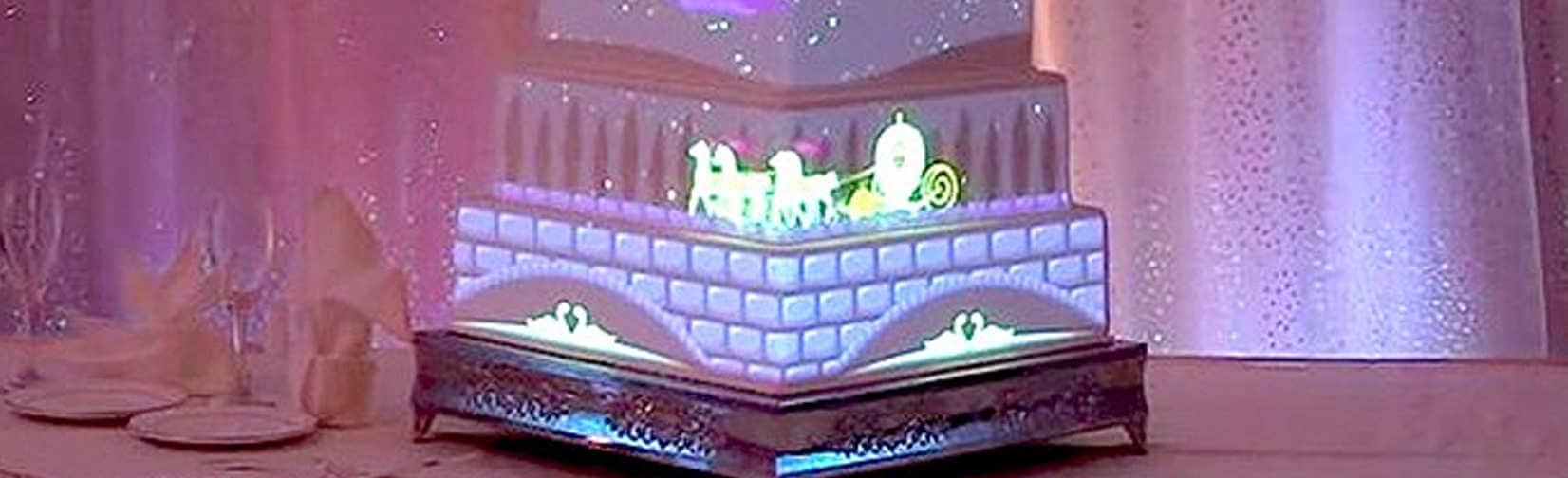 a tiered wedding cake with animations projected onto its surface.
