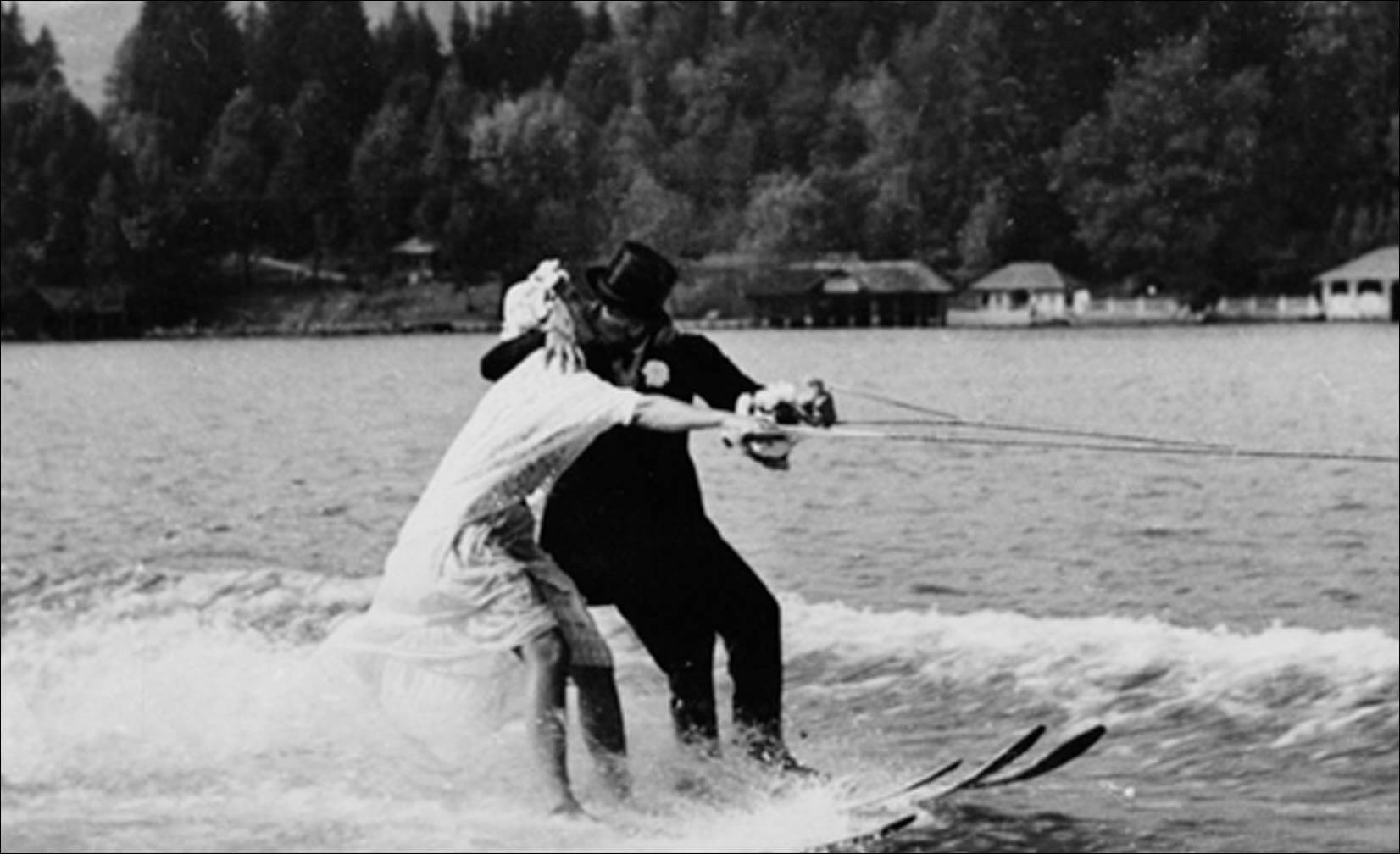 kiss while waterskiing in their wedding attire